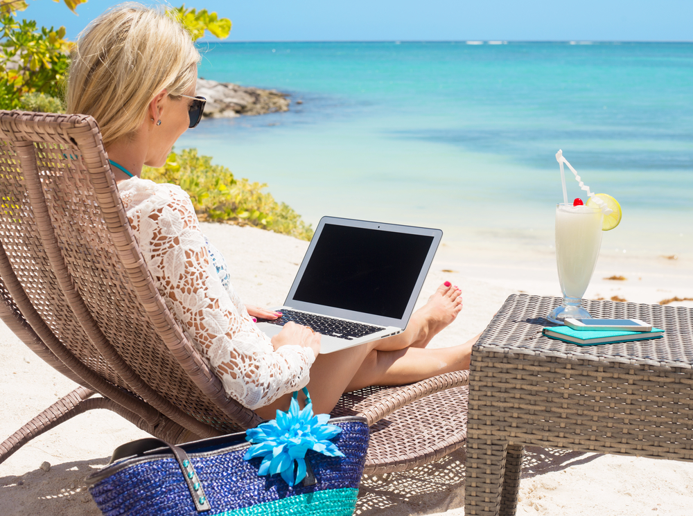 Freelancer working on a beach with a cocktail